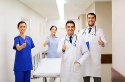 Счастливые доктора показывая большие пальцы руки вверх на больнице Стоковые Фото