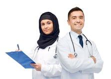Счастливые доктора с доской сзажимом для бумаги и стетоскопами Стоковое Изображение