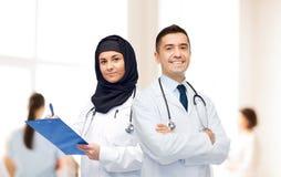 Счастливые доктора с доской сзажимом для бумаги и стетоскопами Стоковая Фотография RF