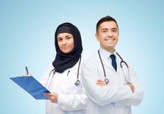 Счастливые доктора с доской сзажимом для бумаги и стетоскопами Стоковое Фото
