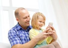 Счастливые отец и дочь с smartphone Стоковое Изображение RF