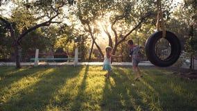 Счастливые отпрыски играя на парке с качанием