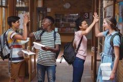 Счастливые одноклассники давая максимум 5 друг к другу в коридоре стоковые фотографии rf