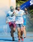 Счастливые пакостные люди бежать на беге цвета Стоковое фото RF