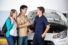 Счастливые пары давая ключи автомобиля к технику Стоковое фото RF