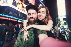 Счастливые пары датировка в влюбленности принимая фото selfie на Таймс площадь в Нью-Йорке пока перемещение в США на медовом меся стоковое изображение