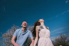 Счастливые пары бежать в саде цветеня держа рука об руку Стоковая Фотография