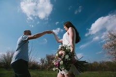 Счастливые пары бежать в саде цветеня держа рука об руку Стоковые Изображения RF