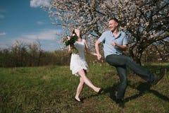 Счастливые пары бежать в саде цветеня держа рука об руку Стоковые Изображения