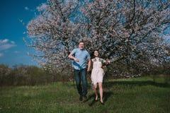 Счастливые пары бежать в саде цветеня держа рука об руку Стоковая Фотография RF