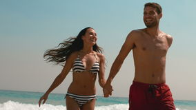 Счастливые пары бежать из воды держа руки сток-видео