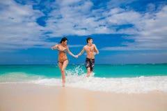Счастливые пары бежать на пляже Стоковые Фотографии RF