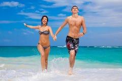 Счастливые пары бежать на пляже стоковая фотография rf