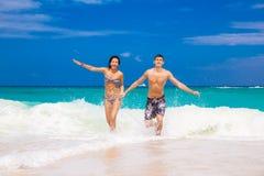 Счастливые пары бежать на пляже стоковые фото