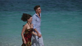 Счастливые пары бежать на тропическом пляже акции видеоматериалы