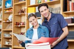 Счастливые пары выбирая бумаги совместно стоковая фотография