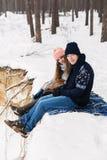 Счастливые пары в лесе зимы сидя на одеяле на пропасти Стоковая Фотография