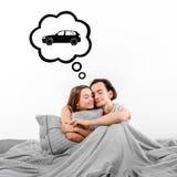 Счастливые пары в кровати мечтая о автомобиле стоковая фотография rf