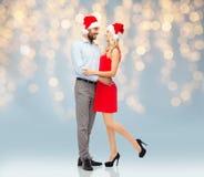 Счастливые пары в обнимать шляп santa Стоковая Фотография