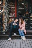 Счастливые пары в теплых одеждах выпивая кофе на рождественской ярмарке Стоковое Изображение RF