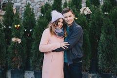 Счастливые пары в теплых одеждах представляя на рождественской ярмарке Стоковое Фото