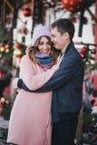 Счастливые пары в теплых одеждах представляя на рождественской ярмарке Стоковые Изображения RF