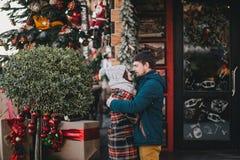 Счастливые пары в теплых одеждах представляя на рождественской ярмарке Стоковая Фотография