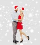 Счастливые пары в шляпах santa обнимая над снегом Стоковое Фото