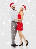 Счастливые пары в шляпах santa обнимая над снегом Стоковая Фотография