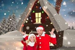 Счастливые пары в santa костюмируют показывать против цифров произведенной предпосылки Стоковая Фотография RF