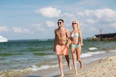 Счастливые пары в swimwear бежать на лете приставают к берегу Стоковое фото RF