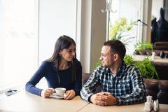 Счастливые пары говоря на кафе, выпивая чае Стоковые Изображения RF