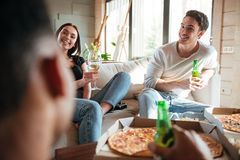 Счастливые пары есть пиццу, выпивая пиво и вино с друзьями Стоковые Изображения