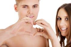 Счастливые пары делая сердце с пальцами Стоковые Фото