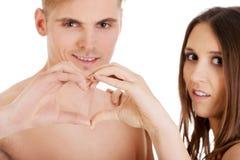 Счастливые пары делая сердце с пальцами Стоковое Изображение