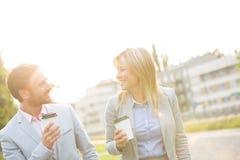 Счастливые пары дела беседуя пока держащ устранимые чашки в городе Стоковое Фото