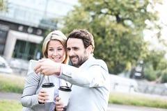 Счастливые пары дела принимая selfie пока держащ устранимые чашки в городе Стоковое фото RF