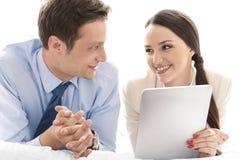 Счастливые пары дела при цифровая таблетка смотря один другого в гостинице Стоковая Фотография RF
