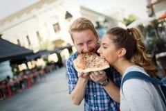 Счастливые пары деля пиццу на улице Стоковое Фото