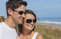Счастливые пары женщины человека в солнечных очках на пляже Стоковое Фото
