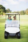 Счастливые пары игрока в гольф сидя в багги гольфа Стоковые Изображения RF