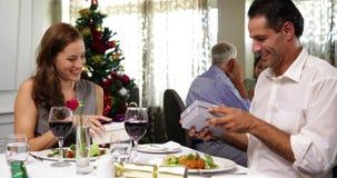 Счастливые пары имея еду рождества совместно и обменивая подарки акции видеоматериалы