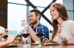 Счастливые пары имея обедающий на ресторане Стоковая Фотография