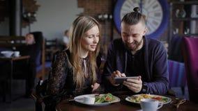 Счастливые пары имея обед совместно и смотря smartphone Человек и женщина используя цифровое устройство смеясь над на изображения сток-видео