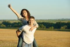 Счастливые пары имея потеху на катании внешних, девушки на задней части человека и мухе - романтичная концепция перемещения и люд Стоковое фото RF