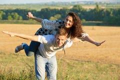 Счастливые пары имея потеху на катании внешних, девушки на задней части человека и мухе - романтичная концепция перемещения и люд Стоковое Изображение