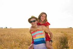 Счастливые пары имея потеху outdoors на пшеничном поле Смеясь над радостная семья совместно черная изолированная свобода принципи стоковые изображения rf