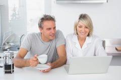 Счастливые пары используя компьтер-книжку в утре стоковое изображение