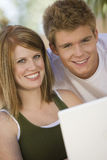 Счастливые пары используя компьтер-книжку Стоковые Фотографии RF