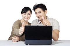 Счастливые пары и компьтер-книжка показывая большие пальцы руки поднимают 2 Стоковые Изображения